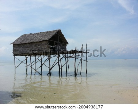 One of the Bajo tribe house ini the island of Muna, Indonesia. The pillars of this house are made of mangrove wood, and the roof is made of thatch leaves. This house stands above the shallow sea.  Photo stock ©