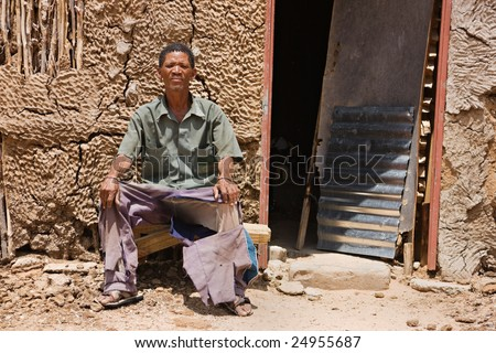 One of the few remaining bushman sitting down in front of his traditional shack, the indigenous people of Kalahari.