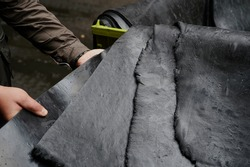 One of the first stages of production of rubber products at the plant. Close-up of raw material seam texture. Medium wholesale manufacturing technology,
