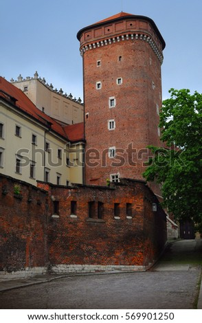 One of the high towers of the Wawel castle in Krakow, surrounded by a red brick wall with loopholes and a fresh green tree. An empty street nearby leads to a gate. Cloudy day in spring #569901250