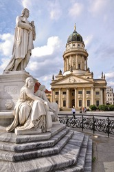 One of the most beautiful squares in Berlin, the Gendarmenmarkt, showing a marble statue of German poet Friedrich Schiller and the French Cathedral in the background.