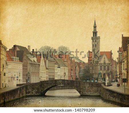 One of the numerous bridges in Brugge, Belgium. Photo in retro style. Paper texture.