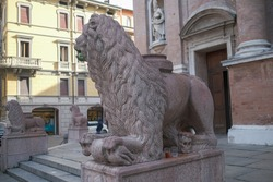 One of the red Verona marble lions guarding the Basilica of San Prospero in Reggio Emilia, Italy. High quality photo
