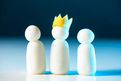 One of the three little men wears a crown. Leadership in the team. The chief directs his subordinates. The official hierarchy. Distribution of roles in the company. Business structure.