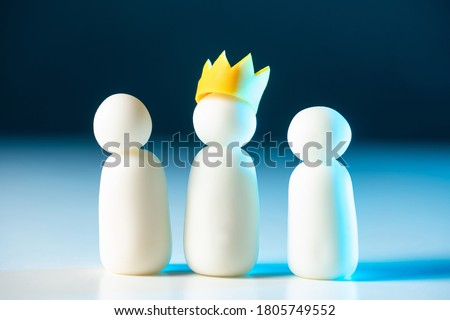 Photo of  One of the three little men wears a crown. Leadership in the team. The chief directs his subordinates. The official hierarchy. Distribution of roles in the company. Business structure.