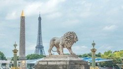 One of the two marble lions of the Tuileries garden overhanging the Concorde place in Paris timelapse, with its obelisk of Luxor and its rostral columns, and the Eiffel Tower in the background
