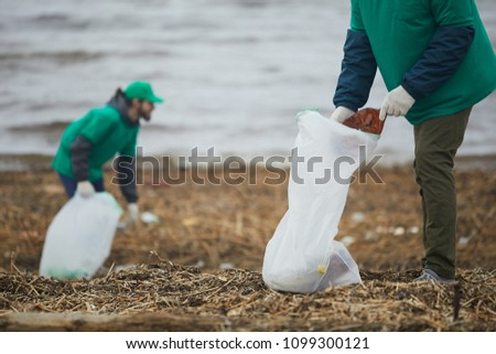 One of two greenpeacers putting smashed plastic bottle into big litter sack while cleaning territory of river bank