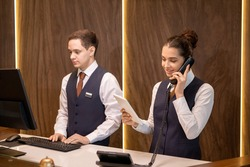 One of two young hotel receptionists standing by counter, looking at touchpad display and consulting client on the phone against colleague