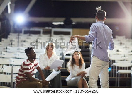 One of young man making speech on stage in front of his coach and groupmates