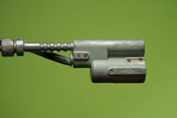 one old closed bicycle lock with a gray metal core and a black cable  on a green background