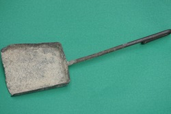 one old gray iron scoop lies on a green table