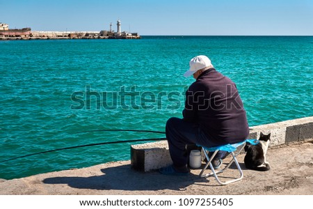 One old man is sitting backwards and fishing at quay with a cat sitting nearby him.