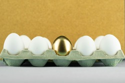 One on anly unique golden egg among plain, simple white eggs in paper tray. Concept of leadership, talent, being gifted and extremely talented.
