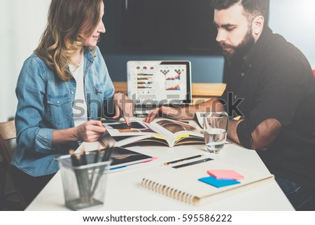 One on one meeting.Business meeting.Teamwork. Businessman and businesswoman sitting at table and watching catalog. On table is laptop and notebook with graphs and diagrams on screen. Online education.
