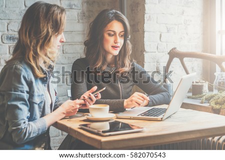One-on-one meeting.Two young business women sitting at table in cafe. Girl shows colleague information on laptop screen. Girl using smartphone, blogging. Teamwork, business meeting. Freelancers working.