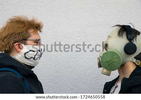 one on one versus confrontation of two man portrait in face respirator mask from diseases and global pandemic and gas mask from environmental pollution and ecology problem, white wall background Stockfoto ©