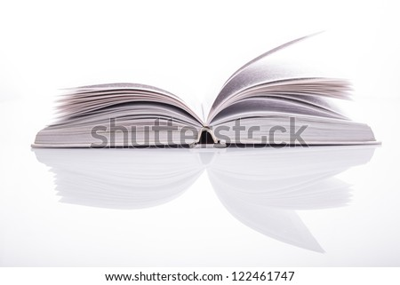One open white book with reflection on white