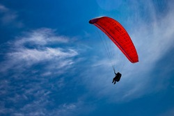 One paraglider is flying in the blue sky. Paragliding on a sunny day.