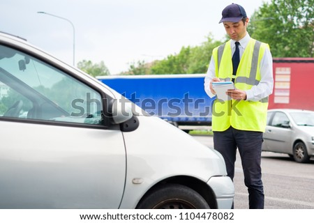 One parking warden writing a ticket for a parking violation Photo stock ©