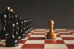 One pawn standing against set of black chess. Alone against many enemies, symbol of difficult fight or struggle, confidence concept