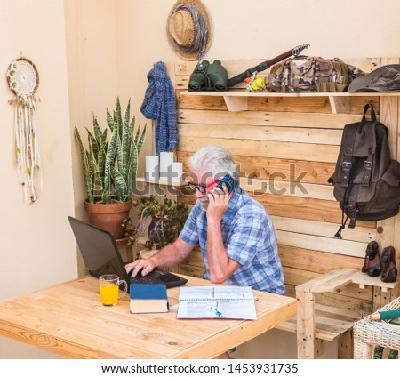 One people, senior man with white hair and beard talking to the phone. Wooden table with laptop and books. Freelance worker doing business in a corner of the terrace
