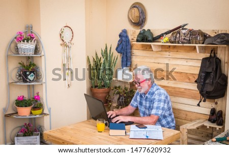 One people, senior man with white hair and beard writing on laptop. Wooden table with laptop and books. Freelance worker doing business in a corner of the terrace