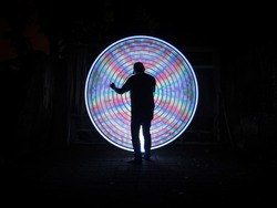 One people standing alone against a abstract circle light painting as the backdrop