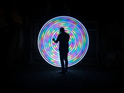 One people standing alone against a incredible abstract circle light painting as the backdrop