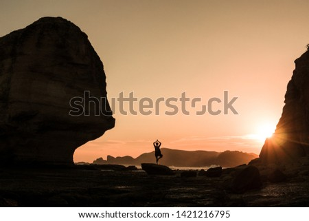 One person in yoga position standing close to beach at warm sunset light. People doing sport fitness with idyllic places in Nature contact. Concept of relaxing time spending outdoor.