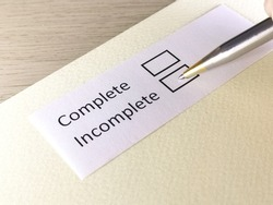 One person is answering question on a piece of paper. The person is thinking to be complete or incomplete.