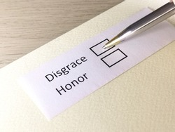 One person is answering question on a piece of paper. The person is thinking to be disgrace or honor.