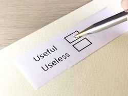 One person is answering question on a piece of paper. The person is thinking to be useless or useful.