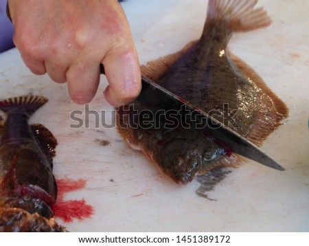 One person is killing a fish with a knife to make a sashimi dish.