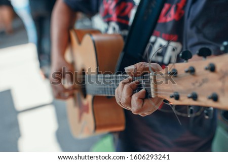 One person is standing playing the guitar with a C chord