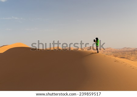 One person on a dune in the desert, holding a touch pad. Landscape