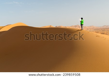 One person on a dune in the desert, holding a touch pad. Sun reflection on the screen. Landscape