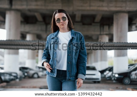One person only. Portrait of beautiful young woman standing under the bridge outdoors.