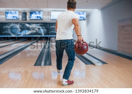 One person only. Rear view of man in casual clothes playing bowling in the club.