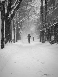 One person silhouette running away in Winter after a snow storm in the streets of Montreal, Canada.  Black and White photography of a lonely jogger.