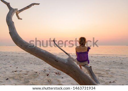 One person sitting on branch sand beach romantic sky at sunset, rear view silhouette, golden sunlight, real people. Indonesia, Kei islands, Moluccas Maluku