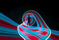 one person standing against beautiful red and blue circle light painting as the backdrop