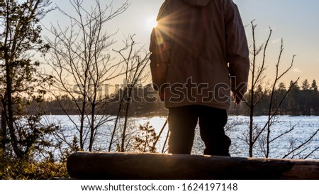 One person stands and looks out over the Swedish river during the sunset during the winter month.