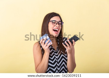 One person waist up beautiful caucasian young women girls in front of peach background who is smiling, happy and cheerful and holding coffee cup, mobile phone. Using smart phone for text messaging