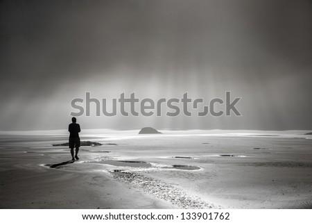 One person walking toward sunbeams on misty beach
