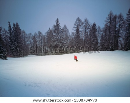 one person wearing a red jacket skiing alone on a ski piste empty of people surrounded by the forest under a snowfall