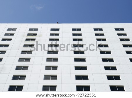 One Photographer takes a shot on the top of building with many windows under blue sky