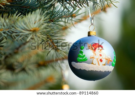 One piece of Christmas decoration of garland, on fir-tree's branch (blue spruce) with green background
