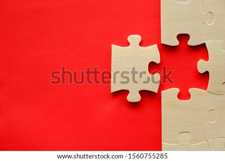 One piece of wood jigsaw next to connected pieces on red background with copy space, shot from top view. Concept for problem solving or teamwork