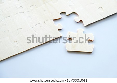 One piece of wood jigsaw next to connected pieces on white background with copy space. Concept for problem solving or teamwork