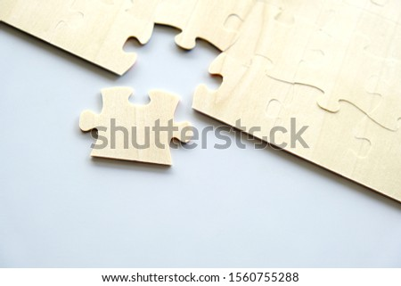 One piece of wood jigsaw next to connected pieces on white background with copy space, shot from top view. Concept for problem solving or teamwork